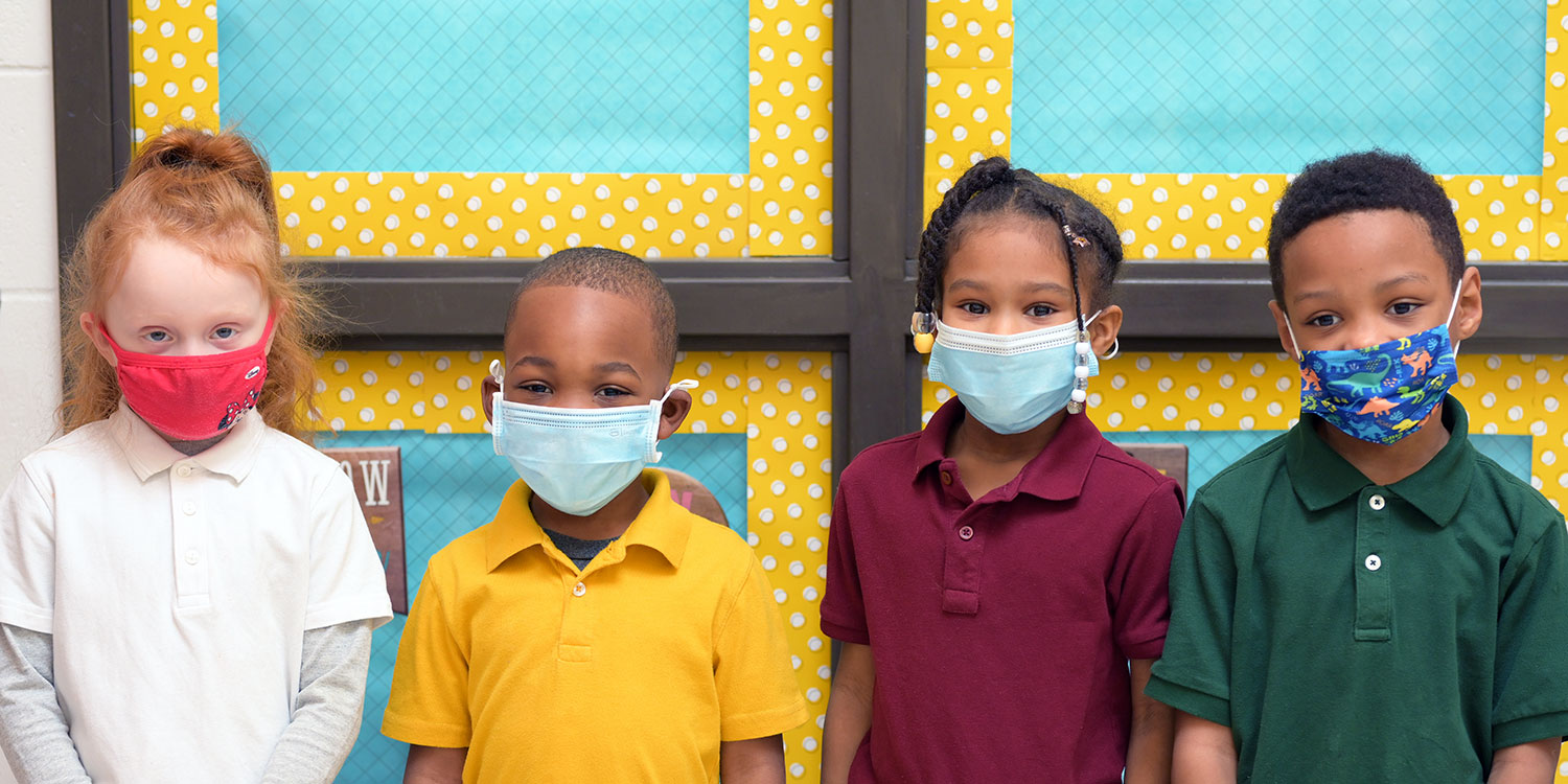 Elementary students in hall wearing masks.