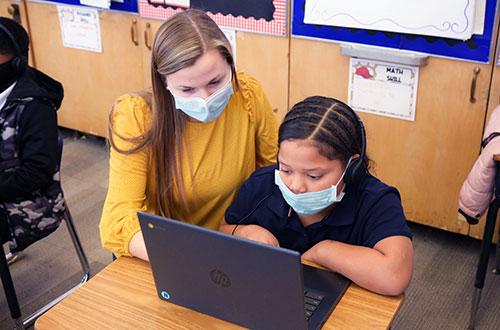 Teacher helping elementary student on laptop.
